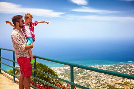 gelukkige vader en zoon genieten van het fascinerende uitzicht op de kustlijn van de Atlantische Oceaan vanaf observatiedek van Pico Isabel de Torres