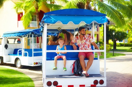 happy tourist family enjoying vacation while riding in vehicle through the hotel area. Transportation service