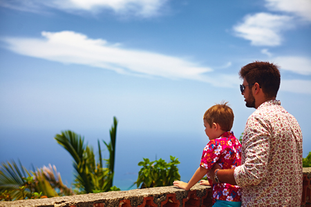 father and son, tourists enjoying the fascinating view on Atlantic ocean coastline from observation deck