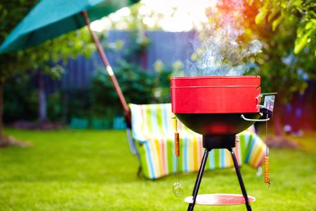 barbecue grill with smoke on summer backyard party