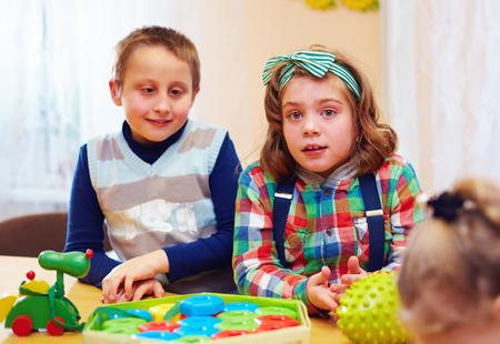 特別なニーズを持つ子供のためデイケア センターで一緒に遊んでいる子供のグループ