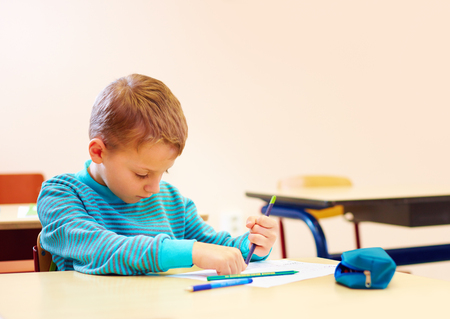 cerebral palsy: cute boy with special needs writing letters while sitting at the desk in class room