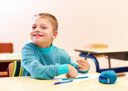 cute boy with special needs writing letters while sitting at the desk in class room
