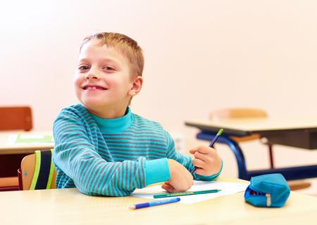 lindo chico con necesidades especiales escribir cartas mientras se está sentado en el escritorio en sala de clase Foto de archivo