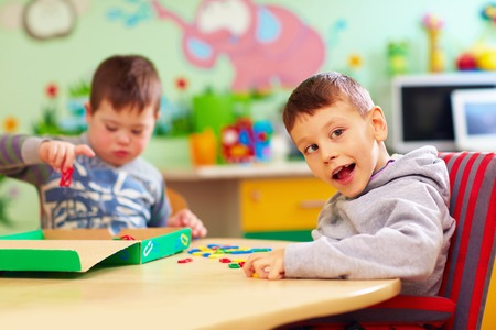 cute kids with special needs playing with developing toys while sitting at the desk in daycare center Banco de Imagens - 74987515