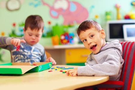 Niños lindos con necesidades especiales jugando con juguetes en desarrollo mientras se está sentado en el escritorio en la guardería