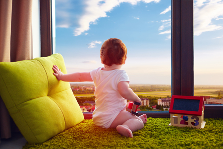 Bebé recién nacido sentado sobre una alfombra en su casa y ve el hermoso paisaje urbano a través de la ventana Foto de archivo - 74987513