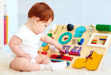 linda del bebé del niño que juega con ocupada bordo en el hogar