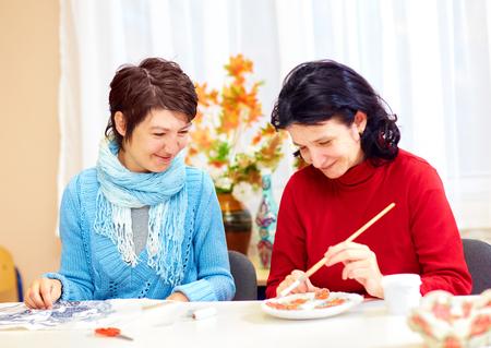 특별한 필요성을 지닌 성인 여성이 재활 센터에서 공예에 종사하고있다.
