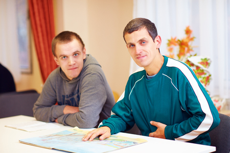 cheerful adult men with disability sitting at the desk in rehabilitation center Stockfoto