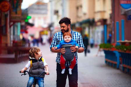paternal: happy father and two sons on the city walk. Parental leave. Baby carrier