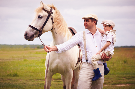 portrait of farmer family standing on the field with horse