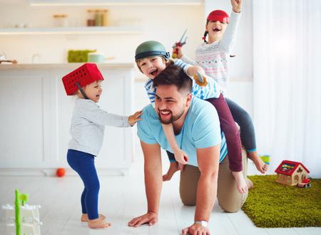 Famille heureuse de jouer ensemble à la maison, à cheval sur le père Banque d'images - 76849112
