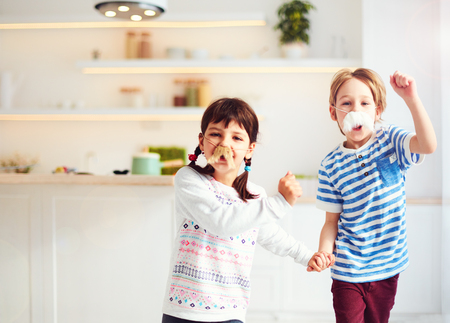 excited kids with mustaches having fun on kitchen at home Imagens