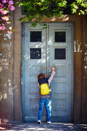 young boy opening the rusty old house door Stock Photo