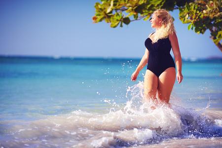 Jeune femme taille plus en maillot de bain profiter de vacances dans les éclaboussures de l'eau sur la plage Banque d'images - 76849110