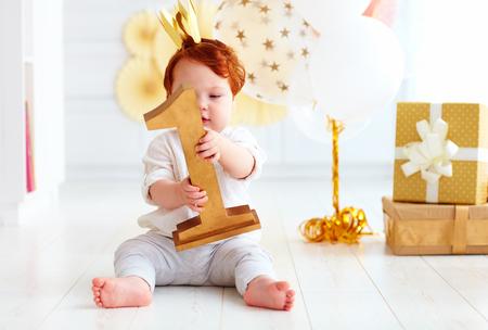 Schattige kleine babyjongen die nummer één houdt, terwijl hij op feestachtergrond zit Stockfoto - 77489482