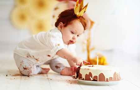 Curioso ragazzo infilare il dito nella sua prima torta di compleanno Archivio Fotografico - 77450589
