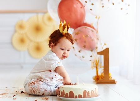 彼の最初の誕生日のケーキに指を突っつい好奇心が強い男の子 写真素材