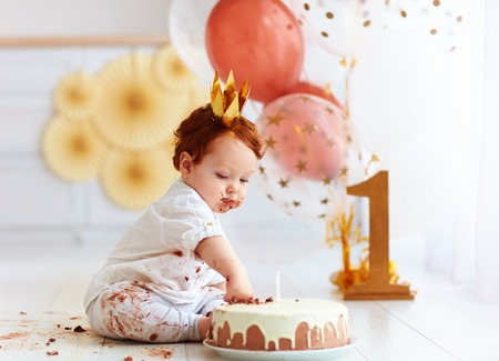 curious baby boy poking finger in his first birthday cake Reklamní fotografie - 77489483