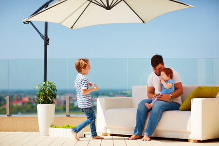 happy family relaxing on couch at roof top terrace at warm sunny day Banco de Imagens