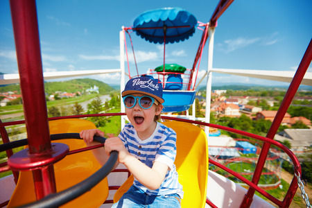 excited kid riding on ferris wheel in amusement park Stockfoto