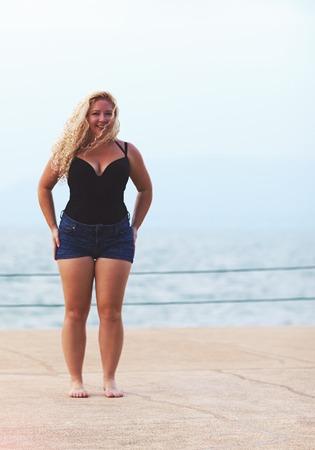 happy plus size jonge vrouw in de buurt van de zee