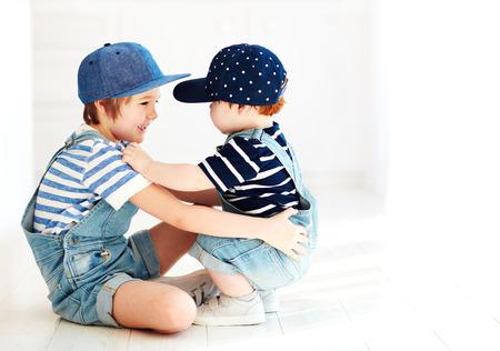 Niños lindos, hermanos en denim monos de comunicación, en el interior