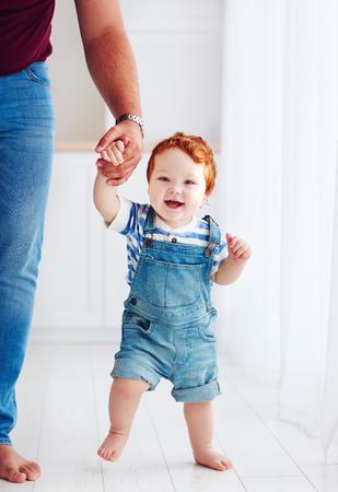 父の助けを借りて歩いている愛らしい幸せな幼児少年