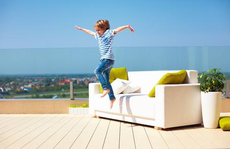 행복 한 아이, 따뜻한 맑은 날에 옥상 테라스에 소파에서 점프하는 소년