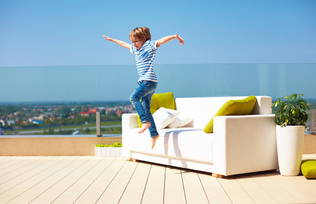 happy kid, boy jumping from the couch on roof top terrace at warm sunny day Stock Photo