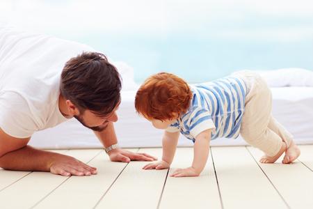 床に彼の幼い息子と遊ぶ父