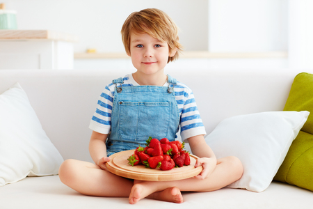 portait: cute kid sitting on couch with a tray of tasty, ripe strawberry Stock Photo