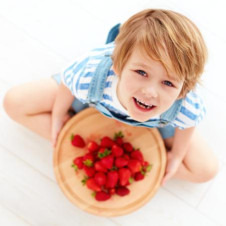 happy kid with a tray of tasty ripe strawberries Фото со стока
