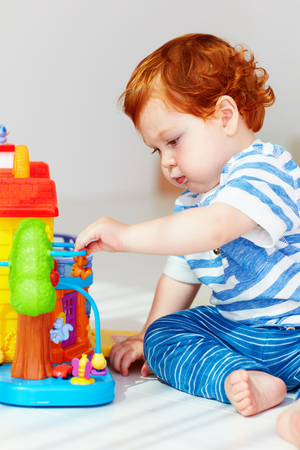cute house: cute little redhead baby playing with toy house Stock Photo
