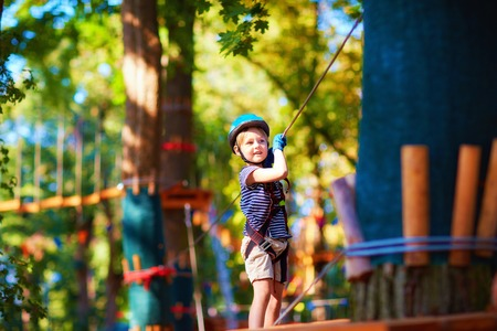 young boy passing the cable route high among the trees, extreme sport in adventure park Stock Photo