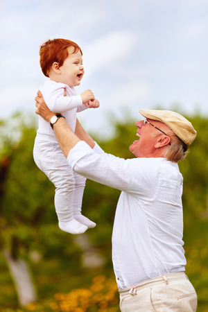 happy grandpa playing with infant grandson in spring garden Stock Photo