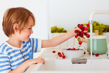 cute young boy washing the armful of sweet cherries under tap water in the kitchen Stock Photo