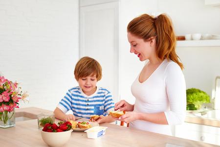 幸せな母と息子の家庭の台所で朝の軽食を準備