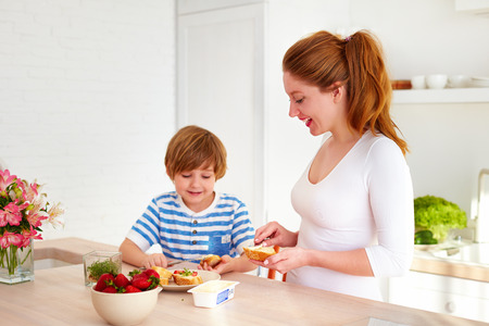 happy mother and son preparing snacks in the morning at home kitchen
