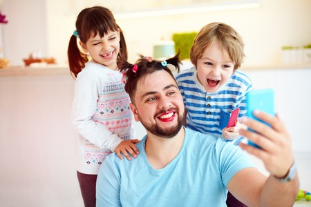 making selfie snap shot with crazy hairstyle and makeup when you home alone with children Stock Photo - 81119857