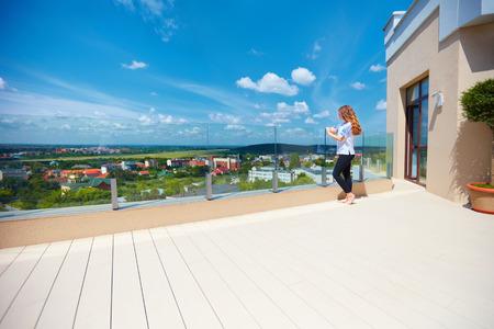 현대 옥상 테라스에 서있는 계곡에서 도시의 아름다운 경치를 즐기고있는 소녀