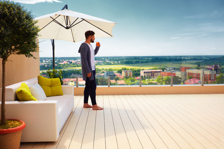 young adult man standing on rooftop terrace, enjoying beautiful cityscape view