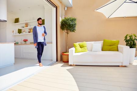 잘 생긴 남자는 열린 공간 주방과 슬라이딩 도어가있는 옥상 테라스에서 인생을 즐깁니다.