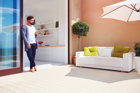 handsome man enjoys life on rooftop terrace with open space kitchen and sliding doors photo & Man Opening Sliding Glass Doors On Patio At Home Stock Photo ...