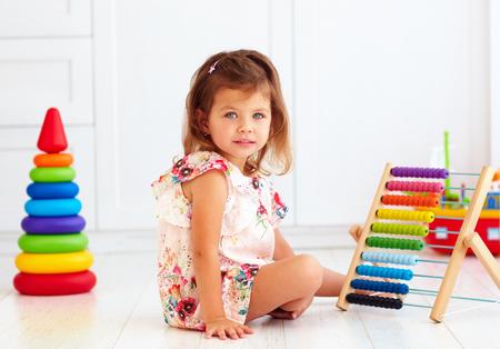 Nettes kleines Mädchen, das mit hölzernem Spielzeug auf dem Fußboden spielt Standard-Bild - 81153854