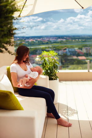 young mother holding on hands infant baby, while sitting on summer patio terrace Stock Photo