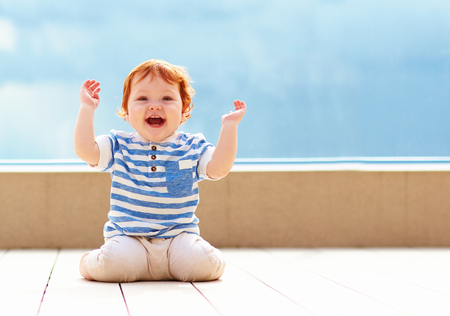 cute excited toddler baby having fun on decking 스톡 콘텐츠