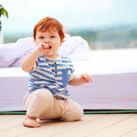cute redhead toddler baby sitting on decking