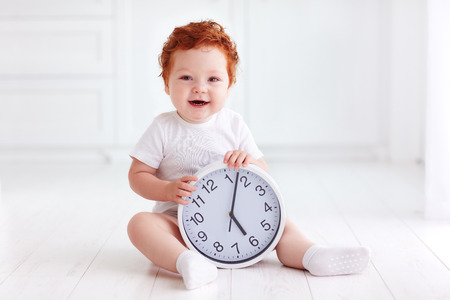 happy little toddler baby holding circle clock Stock Photo - 83530073